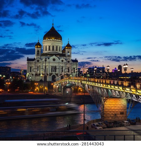 Beautiful illumination of Cathedral of Christ the Savior, Moscow, Russia and Patriarshiy Bridge at Night. Blurred touristic boat at the river, road traffic and sunset sky. - stock photo