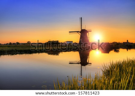 Beautiful image of a dutch windmill at sunset at Kinderdijk in the Netherlands. An UNESCO world heritage site. HDR - stock photo