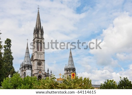 Beautiful image of basilica of the Rosary against blue sky with clouds, Lourdes, France - stock photo