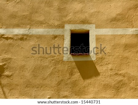 beautiful image of typical mediterranean scenery, little window and shadow on the facade on a sunny day - stock photo