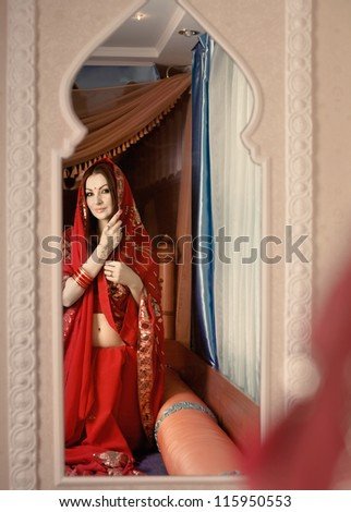Beautiful Indian bride looking in mirror - stock photo