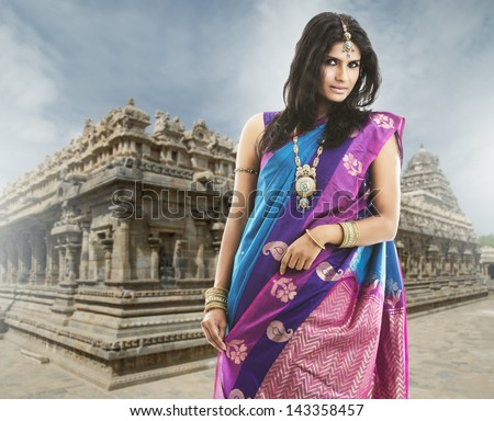 Beautiful Indian girl in traditional Indian sari on temple background. - stock photo