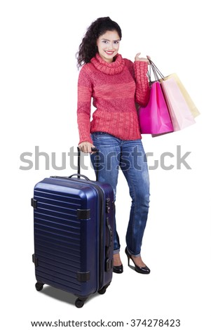 Beautiful indian girl standing in the studio while wearing winter clothes and carrying luggage with shopping bags - stock photo