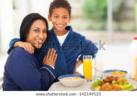beautiful indian mother and son at breakfast table - stock photo
