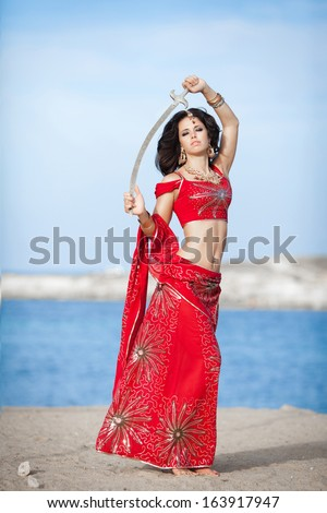 Beautiful Indian woman dancing with golden sword outdoors. Indian dancer girl in traditional red dress in India. Portrait of young Indian woman dancing at sea beach. - stock photo