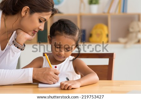 Beautiful Indian woman helping her daughter with homework - stock photo