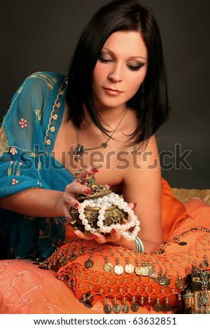 beautiful indian woman laying in ethnic interior - stock photo
