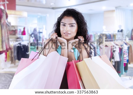 Beautiful indian woman with curly hair, holding shopping bags at shopping center - stock photo
