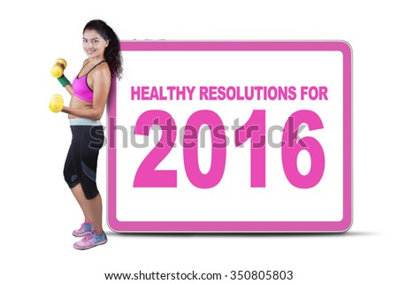 Beautiful indian woman with sportswear and dumbbells, leaning on a billboard with a text of healthy resolution for 2016 - stock photo
