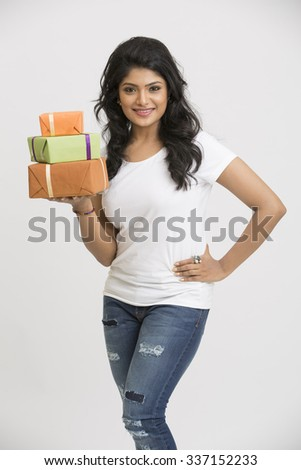beautiful Indian young woman with gift boxes on white background - stock photo