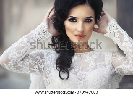 Beautiful innocent brunette bride in white dress posing near church closeup - stock photo
