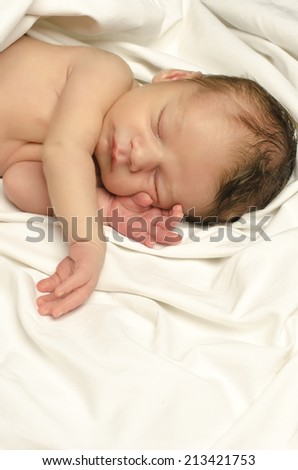 Beautiful innocent newborn sleeping. Adorable little boy relaxing in white sheets after a bath - stock photo