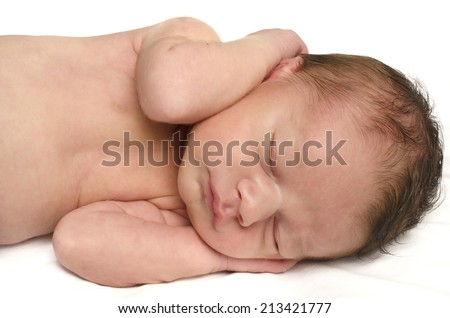 Beautiful innocent newborn sleeping with his hands holding his cute head. Adorable little boy relaxing in white sheets after a bath - stock photo