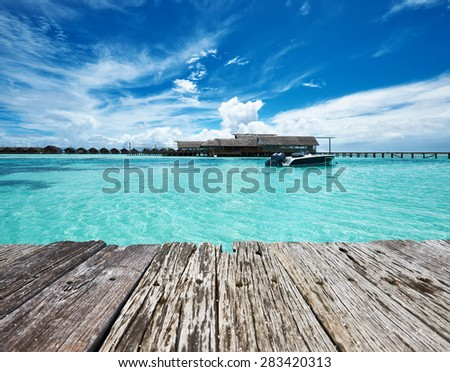 Beautiful island beach and old wooden pier with motor boat at Maldives - stock photo
