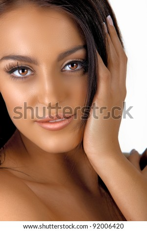 beautiful Italian tanned young woman with natural make-up and long hair holding hand next to her face - stock photo