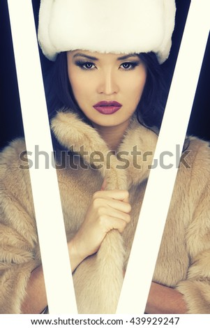 Beautiful Japanese Asian young woman or girl illuminated by glowing fluorescent tubes and wearing (fake) fur hat and coat - stock photo