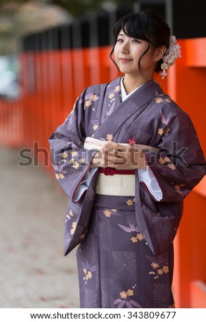 Beautiful Japanese girl dreaming in a seasonal kimono in a traditional Japanese garden during autumn - stock photo