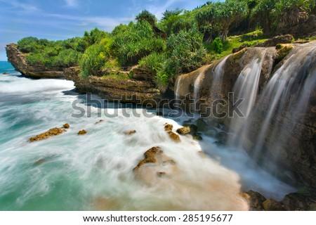 Beautiful Jogan waterfall falling to the ocean, Java, Indonesia - stock photo