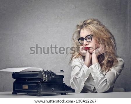 beautiful journalist looks typewriter - stock photo
