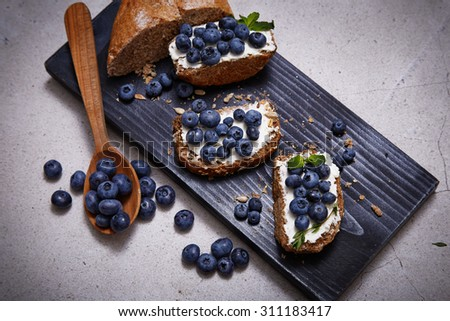 Beautiful juicy ripe natural organic blueberries mint sandwich cheese bread cheese cereal spoon board berries oregano thyme, healthy food diet sweet delicious vitamins breakfast lunch dinner - stock photo