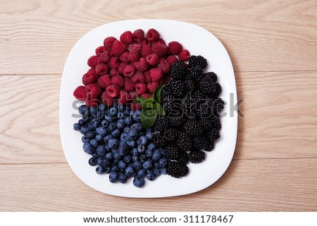 Beautiful juicy ripe natural organic raspberries, blackberries, blueberries lie on a white plate, healthy food diet sweet delicious vitamins for breakfast, lunch or dinner, a good harvest - stock photo