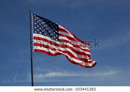 Beautiful jumbo American flag on a flag pole flying against a blue sky - stock photo