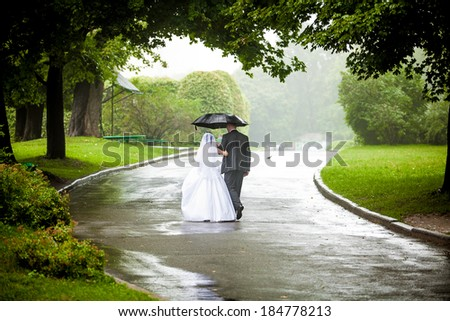 Beautiful just married couple under umbrella walking away on road at park  - stock photo