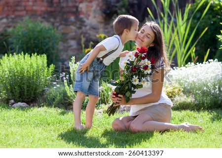 Beautiful kid and mom in spring park, flower and present. Mothers day celebration concept - stock photo