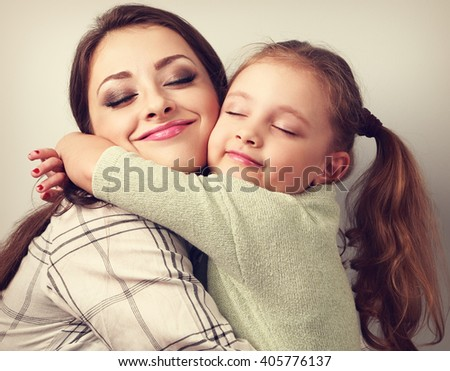 Beautiful kid girl and mother hugging with closed true enjoying. Toned closeup portrait - stock photo