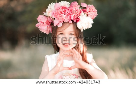 Beautiful kid girl 4-5 year old making heart with hands outdoors. Looking at camera. Childhood.  - stock photo