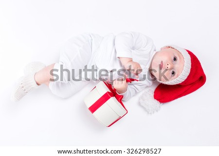 beautiful kid sitting in a New Year's cap and white body among Christmas boxes with gifts lying on his back and looking up, picture with depth of field - stock photo