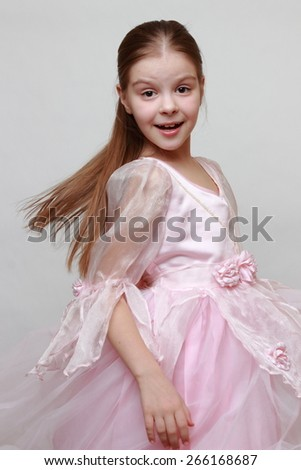 Beautiful kid wearing pink dress as a princess - stock photo