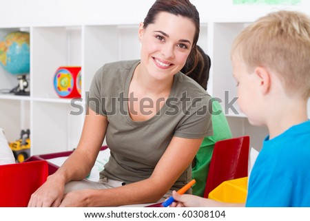 beautiful kindergarten teacher in classroom with kids - stock photo