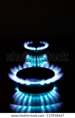 Beautiful kitchen blue gas flames burning, with dark background. Great for cooking and energy themes. - stock photo