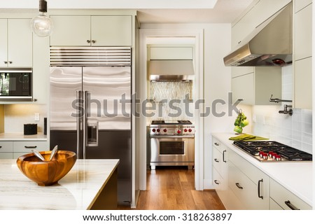 Beautiful Kitchen Interior with Island, Stainless Steel Refrigerator, Oven, Cabinets, and Hardwood Floors in New Luxury Home - stock photo