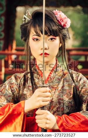 Beautiful korean woman or  geisha in kimono holding samurai sword near face - stock photo