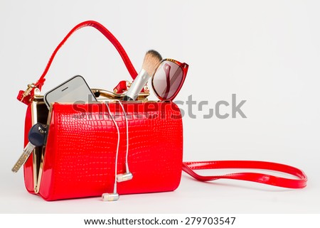Beautiful lacquered red bag with women's accessories. - stock photo