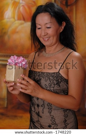 Beautiful lady in a warm setting holding gift - stock photo