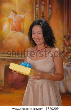 Beautiful lady in a warm setting with a gift - stock photo