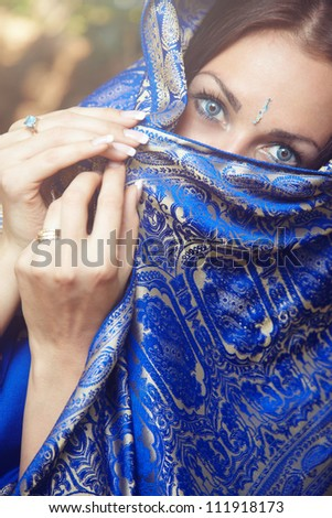 Beautiful lady in blue Indian sari outdoors - stock photo