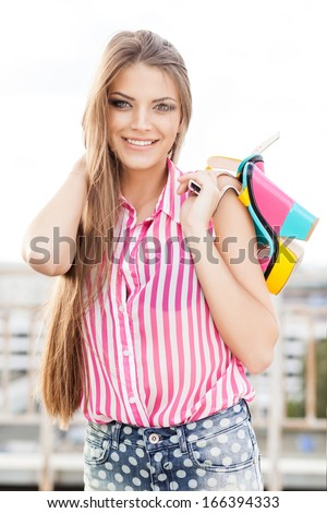 beautiful lady in denim shorts and sleeveless striped top plays with her long silky hair holding bright high heels smiling for camera - stock photo