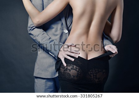 Beautiful lady in dress with guy in suit. Young couple is hugging each other. Portrait of girl with naked body and boy indoors in passionate pose. Beauty woman with attractive lace gown - stock photo