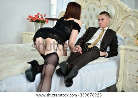 Beautiful lady in dress with guy in suit. Young couple is hugging each other. Portrait of girl with attractive body and boy indoors in passionate pose. Beauty woman with lace gown - stock photo