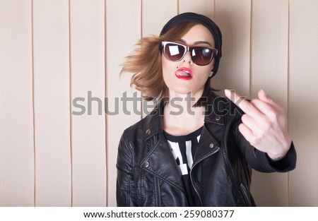 Beautiful lady in leather jacket showing middle finger. - stock photo