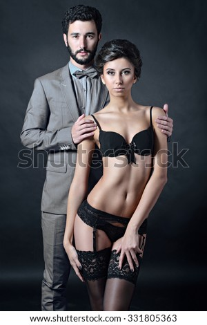 Beautiful lady in panties and bra with guy in suit. Young couple is hugging each other. Portrait of girl in underwear and boy indoors in passionate pose. Beauty woman with attractive lace lingerie - stock photo