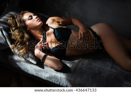 Beautiful lady in sexy lingerie lies on a sofa - stock photo