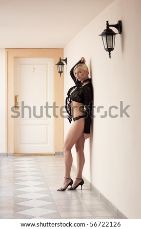 beautiful lady in underwear in front of hotel room doors number seven - stock photo