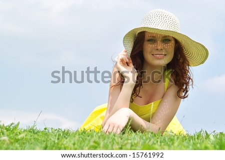 Beautiful lady in yellow dress relaxing in the park - stock photo