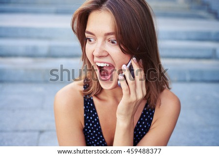 Beautiful lady is listening to her phone interlocuter with the surprised expression on her face over street stairs background - stock photo