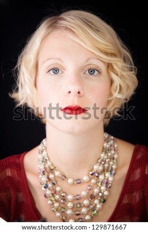 Beautiful lady looking directly at the camera Beautiful lady with an old fashioned style shot in studio with a black background. - stock photo